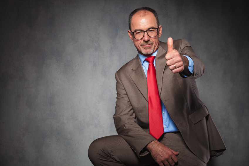 confident senior entrepreneur showing thumbs up